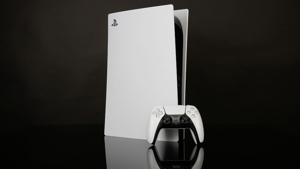 Spielkonsole und Controller vor dunklem Hintergrund.