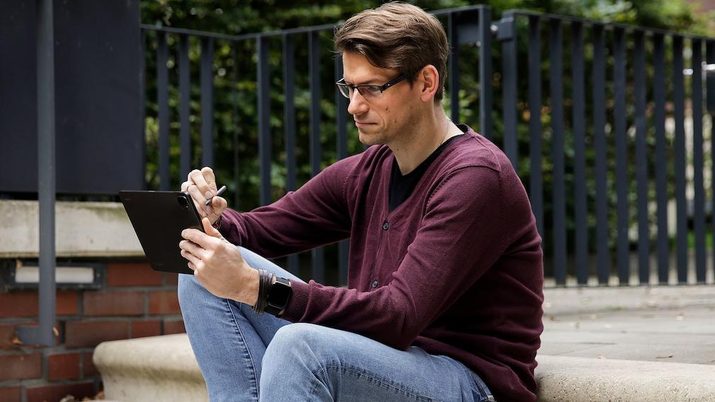 Redakteur schreibt mit Stift auf einem Tablet.