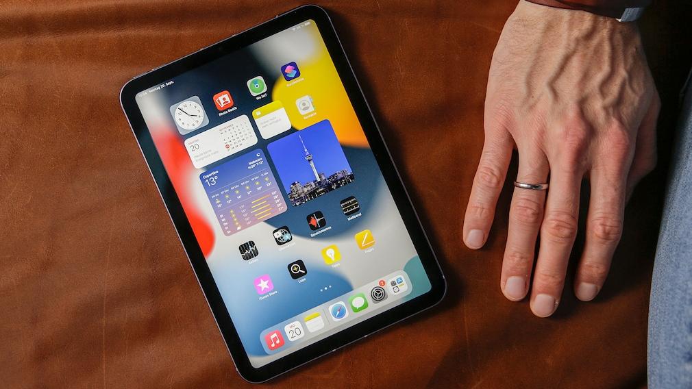 iPad mini liegt auf einem Sofa neben einer Hand.