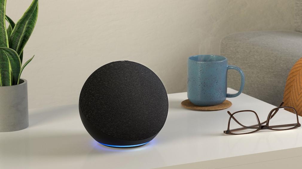Amazon Echo steht auf einem Tisch neben einer Brille.