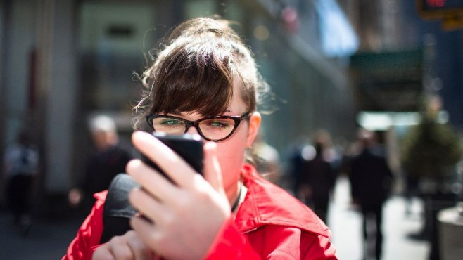 Frau schaut auf ihr Handy im Straßenverkehr©Getty