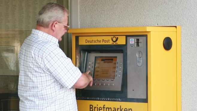 Kunde am Briefmarkenautomat © Deutsche Post AG
