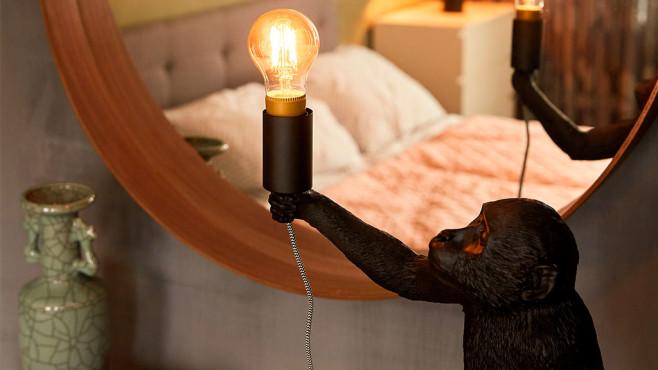 Lampe in Affenform hält eine Filament-Leuchte von Innr. ©Innr