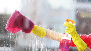 ©Fotolia--Africa Studio-Woman in a rubber glove cleaning window with sponge and detergent, close up