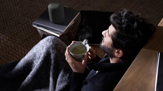 Mann auf einer Couch hört Musik mit dem Nest Audio.©Google LLC