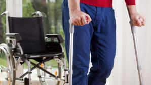 Mann auf Krücken vor dem Rollstuhl©istock.com/KatarzynaBialasiewicz
