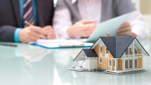 Zwei Menschen unterschreiben Vertrag vor Hausmodell©istock.com/AlexRaths