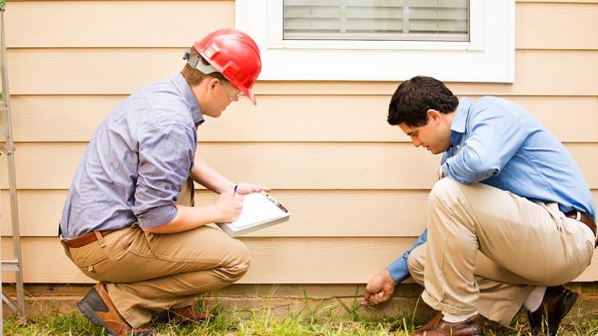Zwei Männer begutachten eine Häuserwand©istock.com/fstop123